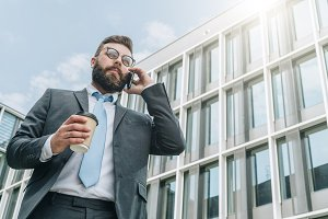 Young businessman in suit and tie is standing outdoor, drinking coffee and talking on his cell phone.