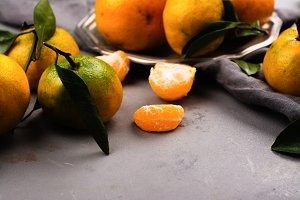 Tangerines with leaves on stone table. Top view