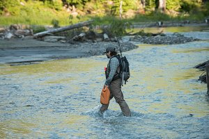Side view of man with backpack walking in river