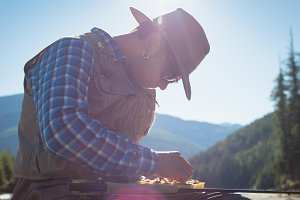 Man removing fishing bait from box while sitting against sky