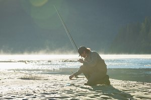 Side view of man with fishing rod while kneeling on riverbank