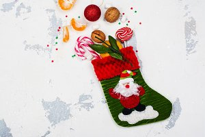 Christmas sock full of holiday gifts on white backgound