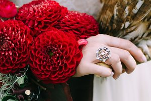 Bouquet with bordeaux dahlias on bride hand. Vintage ring. Wedding decoration.