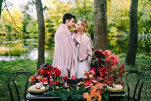 Newlyweds hugging under the plaid next to the festive table. Bride and groom in the park. Autumn wedding. Artwork