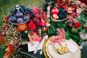 The festive wedding table with red autumn leaves. Wedding decoration. Artwork