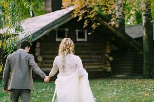Bride and groom go to wooden home in the forest. Autumn wedding. Artwork