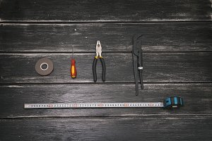 Top view of Working tools - screwdriver, adjustable wrench, pliers, duct tape and tape measure on the wooden background