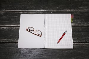 White notebook, pen and glasses on a black wooden background