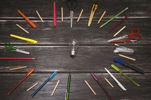 Stationery - colorful pencils and stuff equipment - light bulb in the center on wooden background