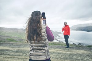 Tourists photographing each other against the background of a beautiful landscape in Iceland.