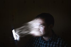 Concept Internet of dependence, submission. Man sucked into a phone. The man's face is transferred to the smartphone screen