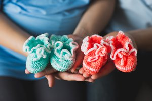 Cuty baby shoes in the hands of expectant parents