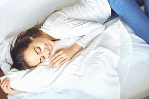 young woman lying on bed hugging pillow
