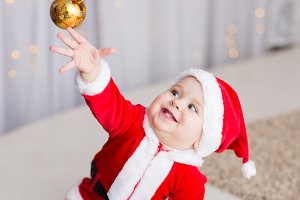 funny baby boy weared in Santa hat with golden Christmas ball