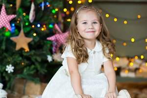 Very nice charming little girl blonde in white dress smile on the background of Christmas trees in in cozy home interior