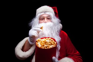 Christmas. Photo of Santa Claus gloved hand With a red bucket with popcorn, on a black background