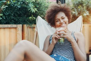 Smiling black girl with beverage