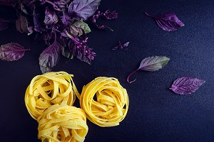Pasta with purple basil on dark background