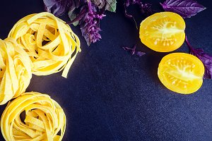 Pasta with purple basil and yellow tomatoes on dark background