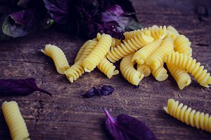 Pasta with purple basil on wooden background