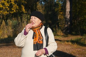 Elderly senior woman make-up lips in autumn forest, portrait