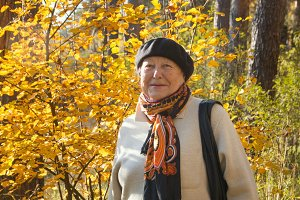 Portrait of elderly senior woman in hat at autumn park