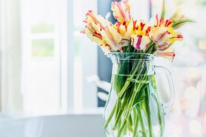 Tulips bunch in vase on window