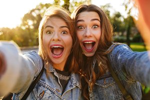 Portrait of two excited young girls making funny faces