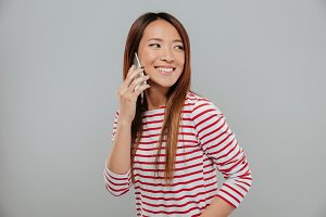 Portrait of a cheery asian girl talking on mobile phone