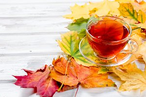Hot tea and colorful autumn leaves