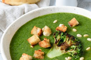 Broccoli cream soup with croutons in white bowl. Closeup view