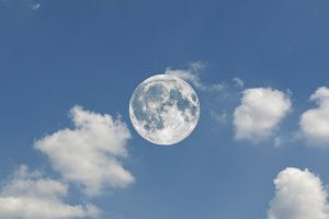 Full moon seen with telescope over blue sky