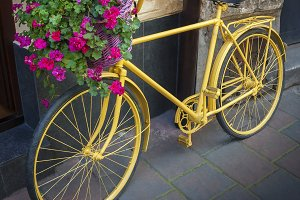 Yellow bicycle with flower basket