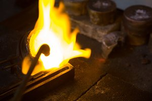Welding torch and metal piece in workshop