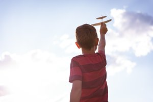 Boy playing with toy aeroplane