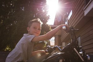 Portrait of cute boy sitting on motorcycle