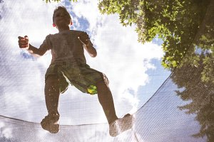 Boy standing on net in playground