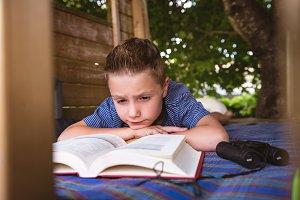 Boy reading in log cabin