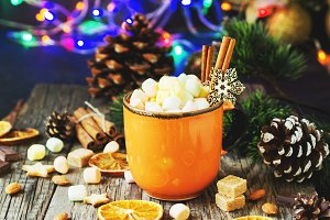 a cup of Christmas hot cocoa with marshmallow New Year's lights and decorations, selective focus