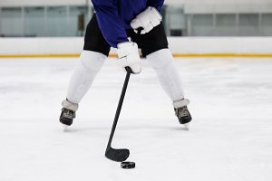 Low section of player playing ice hockey at rink
