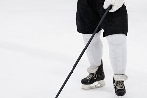 Low section of player with hockey stick at ice rink