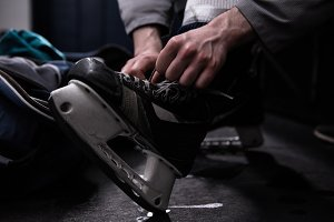 Low section of player tying ice skate