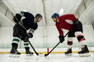 Male hockey players looking face to face at rink