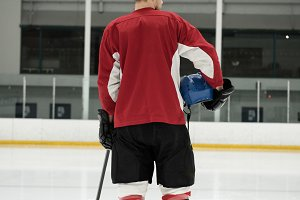 Rear view of ice hockey player holding helmet