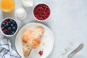 Fresh croissant, berries, honey and berries on table. Top view