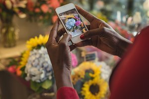 Female florist taking photograph of flower bouquet