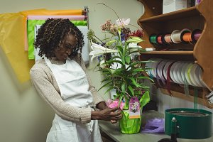 Female florist preparing a flower pot