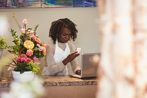 Female florist using laptop and mobile phone