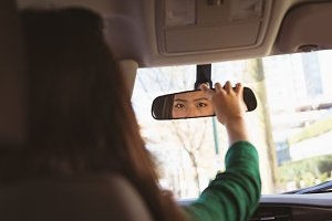 Woman looking into rear view mirror while driving a car