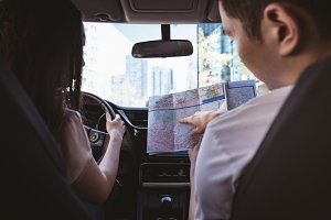 Couple using map in the car